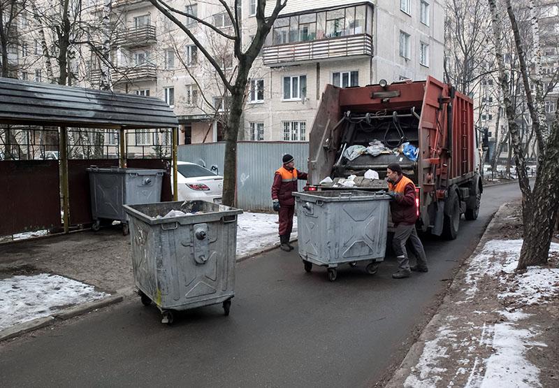 Сотрудники коммунальных служб выгружают мусор из контейнеров