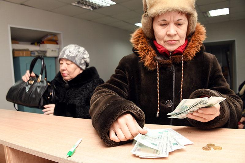 Женщина пересчитывает полученную пенсию