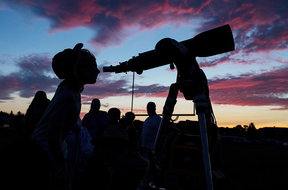 Люди смотрят в телескоп