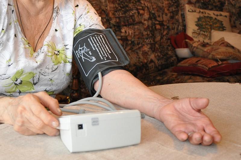 Пожилая женщина за столом тонометром измеряет давление