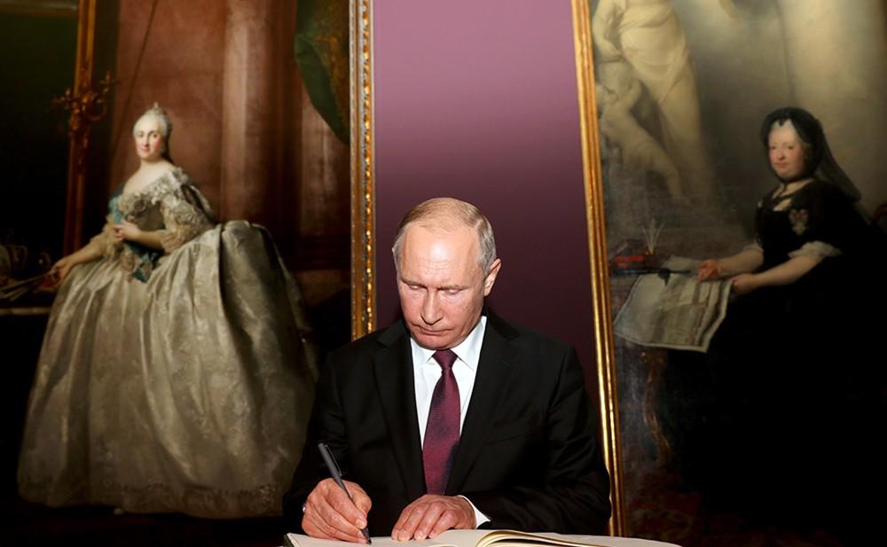 Президент России Владимир Путин подписывает документ