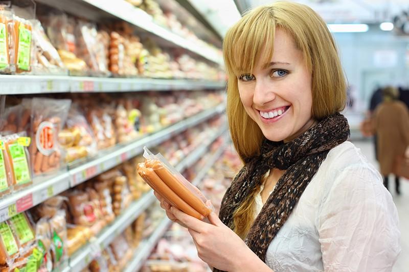 Девушка покупает сосиски в магазине