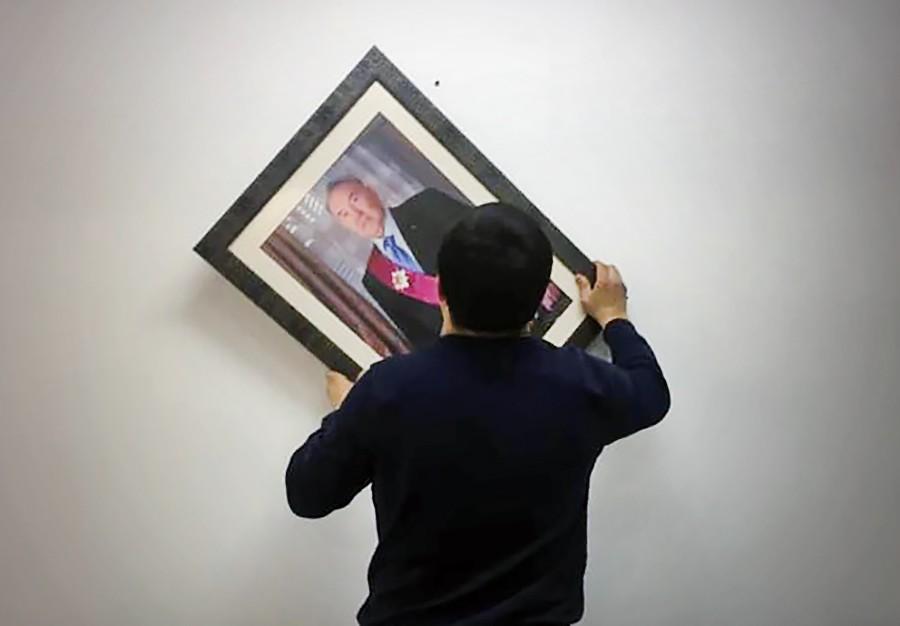 Мужчина снимает портрет Нурсултана Назарбаева