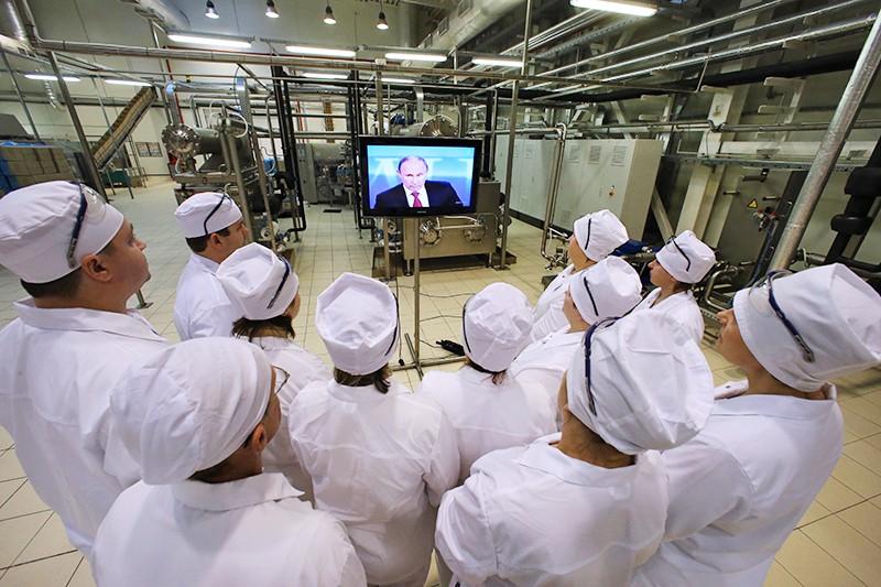 Работники пищевого предприятия смотрят телетрансляцию пресс-конференции президента России Владимира Путина