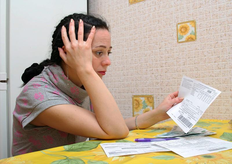 Женщина с квитанциями на оплату квартиры