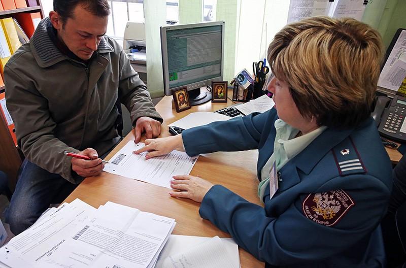 Сотрудница федеральной налоговой службы общается с налогоплательщиком