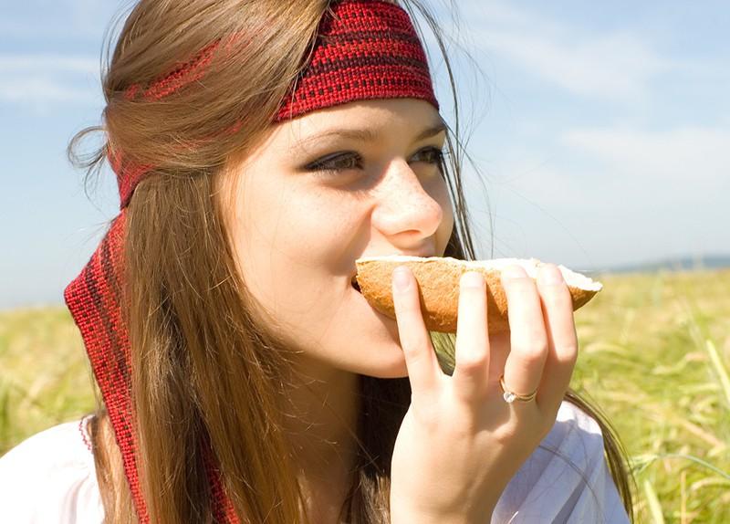 Девушка ест хлеб с маслом