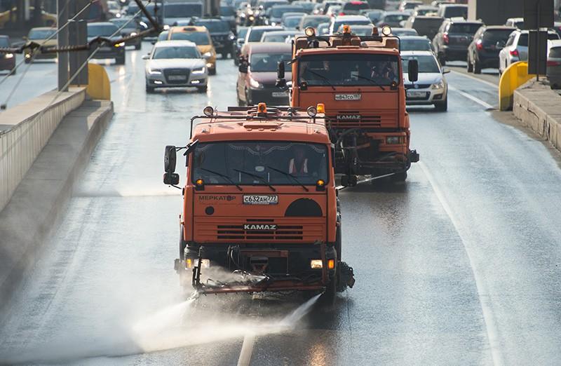 Поливомоечные машины обрабатывают улицу моющим средством в Москве