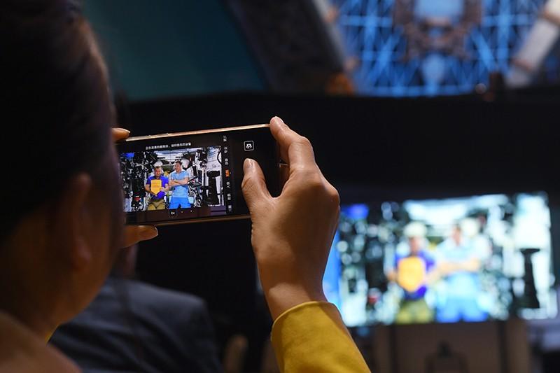 Зрительница снимает на телефон обращение экипажа МКС