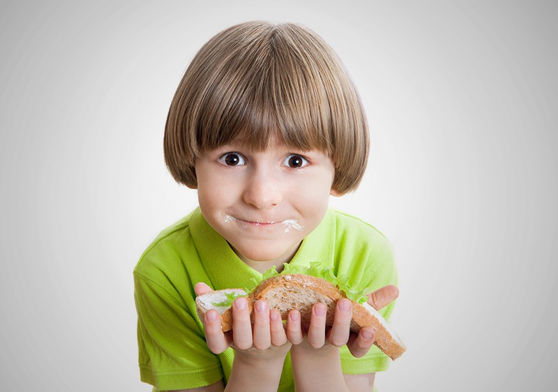 Мальчик ест бутерброд