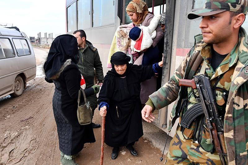 Сирийские беженцы пересекают гуманитарный коридор
