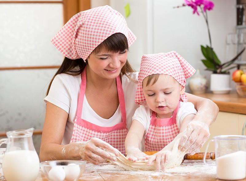 Молодая мама замешивает тесто с ребенком
