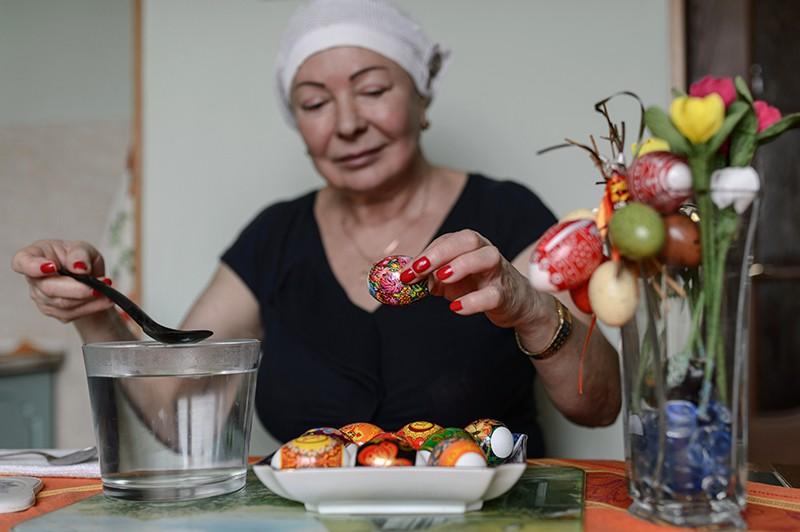 Женщина украшает пасхальные яйца