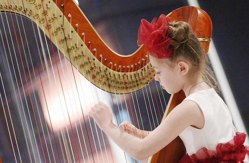 Девочка играет на арфе