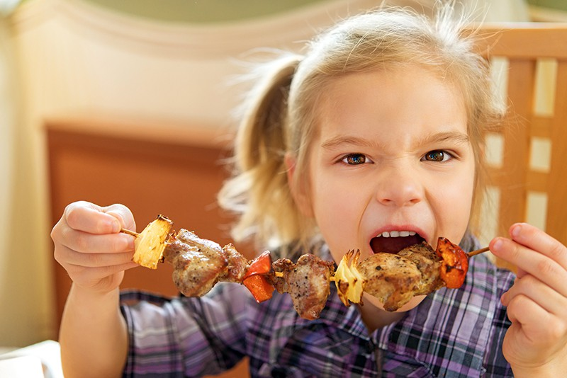 Девочка ест шашлык