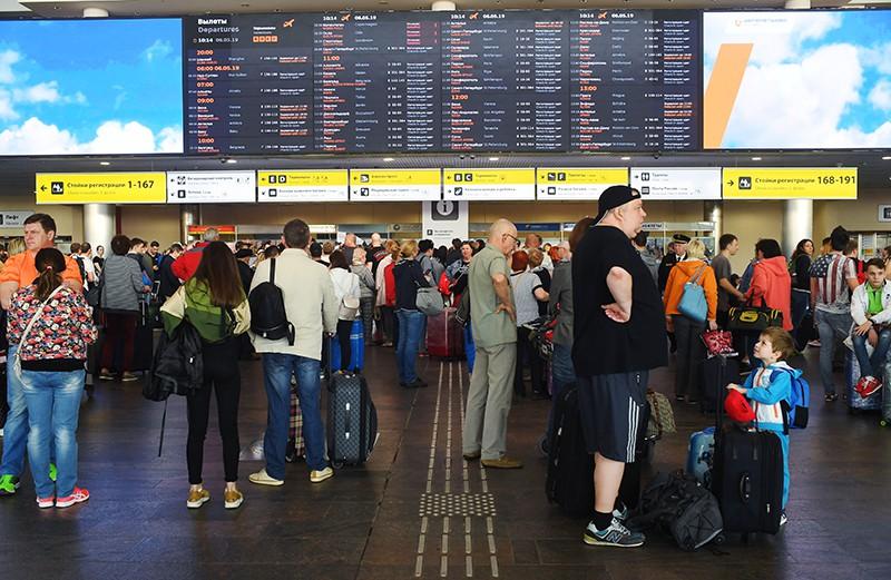 Пассажиры у табло рейсов в аэропорту Шереметьево
