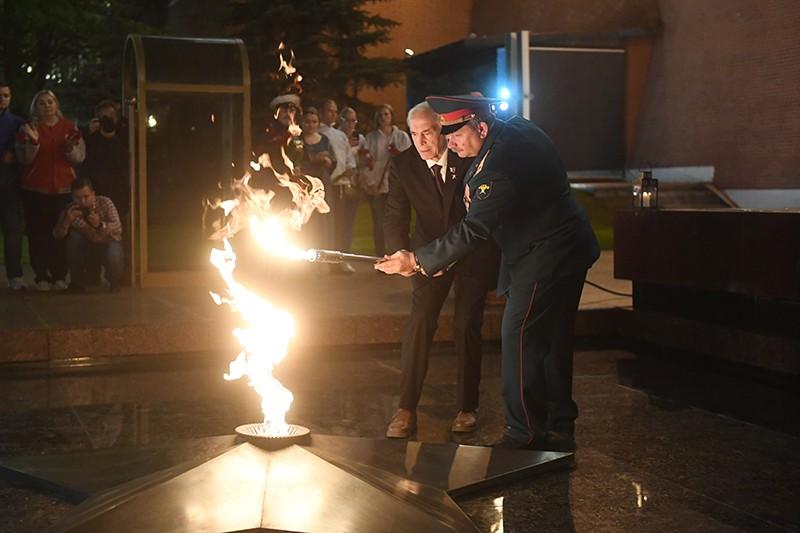 Актер Василий Лановой зажигает с помощью факела Вечный огонь