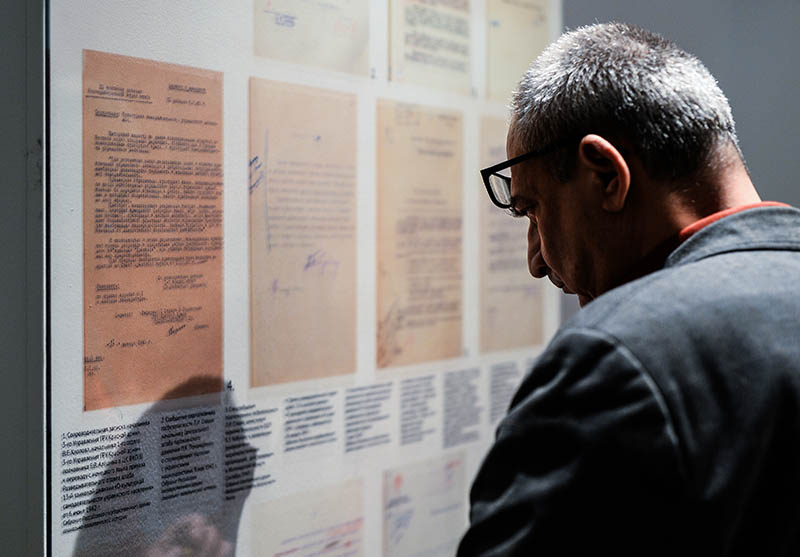Посетитель рассматривает стенд с архивными документами