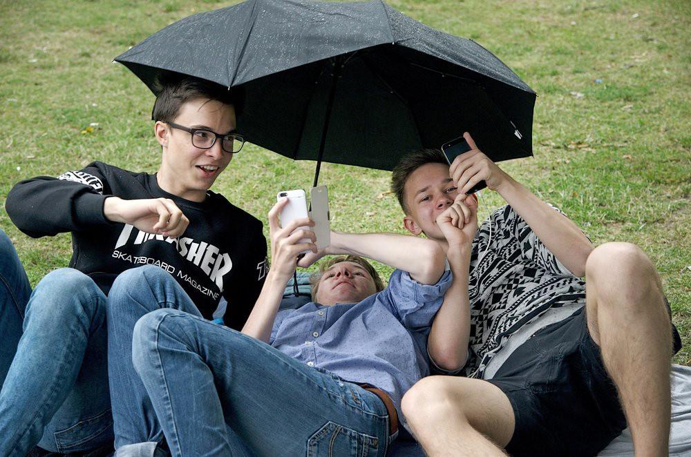 Молодые люди со смарфонами под зонтом