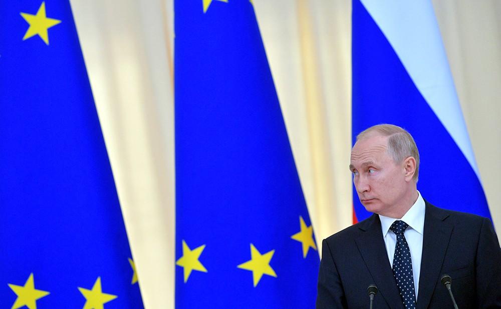 Владимир Путин на фоне флагов Евросоюза