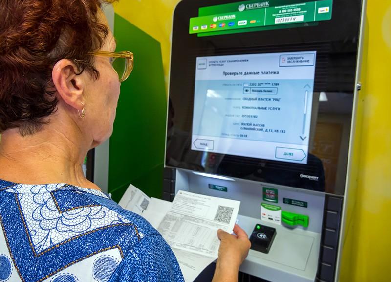 Пожилая женщина оплачивает в терминале