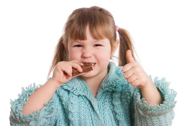 Счастливая девочка ест конфеты