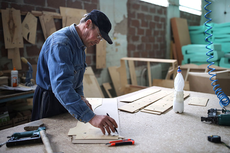 Сотрудник делает заготовки мебели в цехе деревообработки
