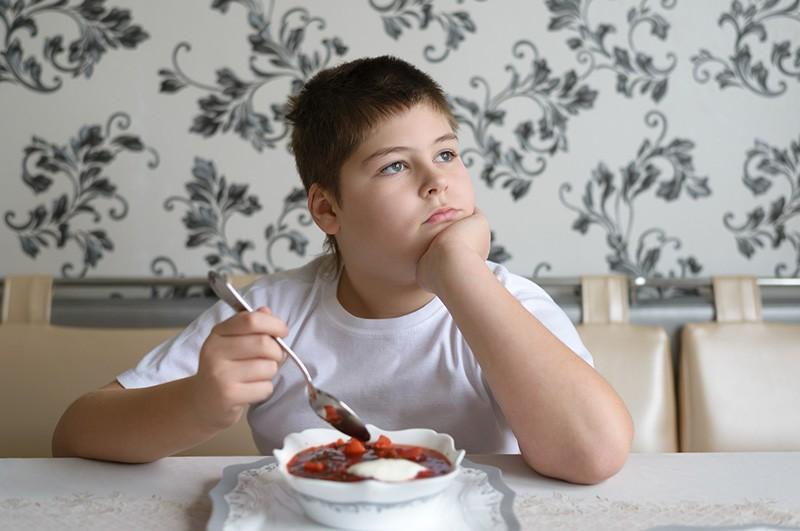 Мальчик ест суп