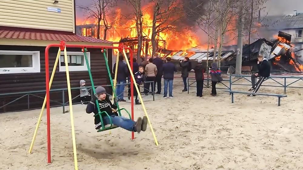 Мальчик качается на качелях на фоне пожара