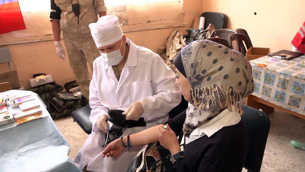 Военный врач осматривает жителей Сирии