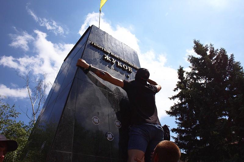 Представители националистических организаций сбивают надпись под бюстом маршала Георгия Жукова