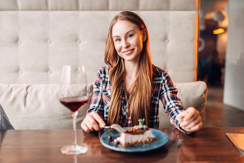 Девушка пьет вино и есть торт