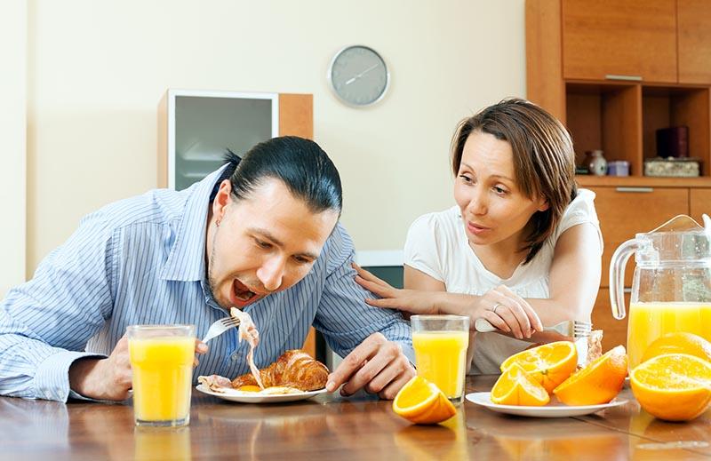 Мужчина ест яичницу