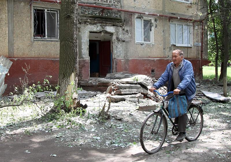 Мужчина едет на велосипеде во дворе жилого дома, пострадавшего в результате обстрела, в поселке Горловка Донецкой области