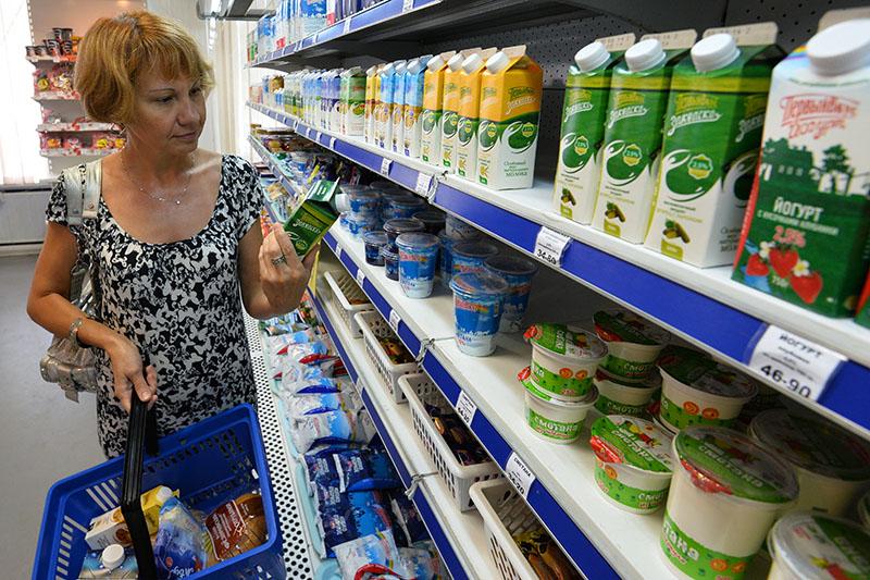 Покупательница у полки с молочной продукцией в магазине