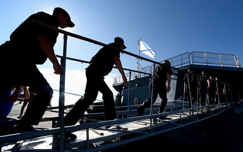 Военные моряки поднимаются на корабль