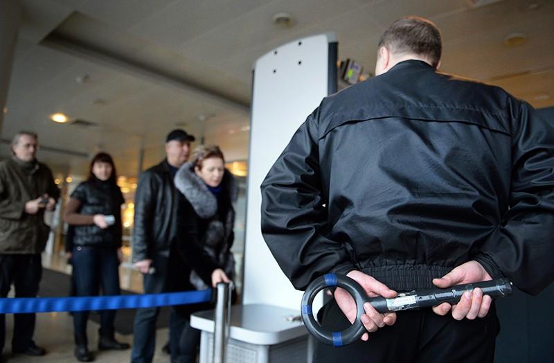 Пассажиры проходят контроль безопасности на входе в аэропорт