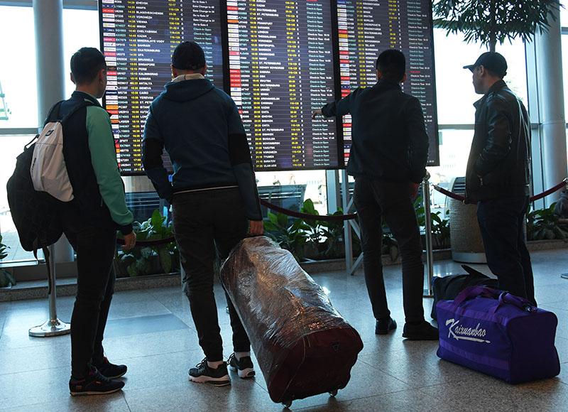 Пассажиры у информационного табло в аэропорту