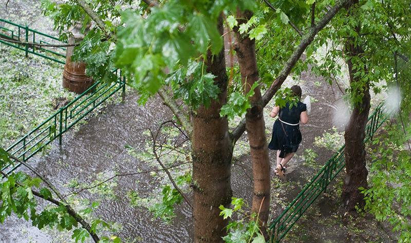 Девушка бежит по улице во время дождя и града