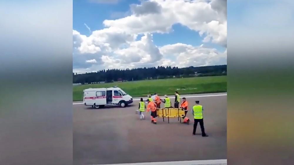 Врачи ведут пилота самолета на обследование