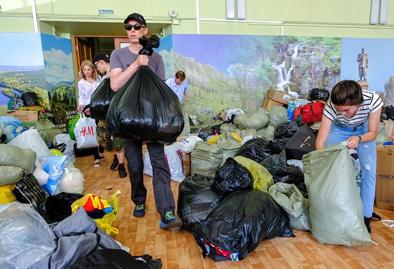Люди собирают гуманитарную помощь