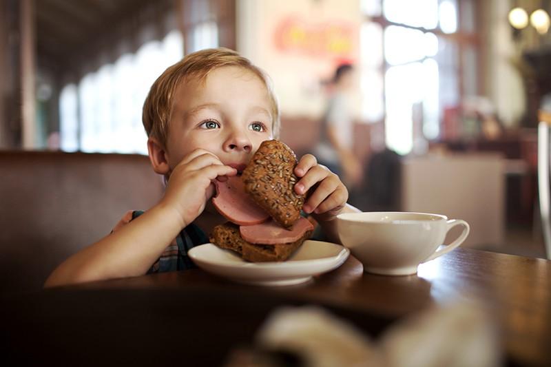 Ребенок ест хлеб с колбасой