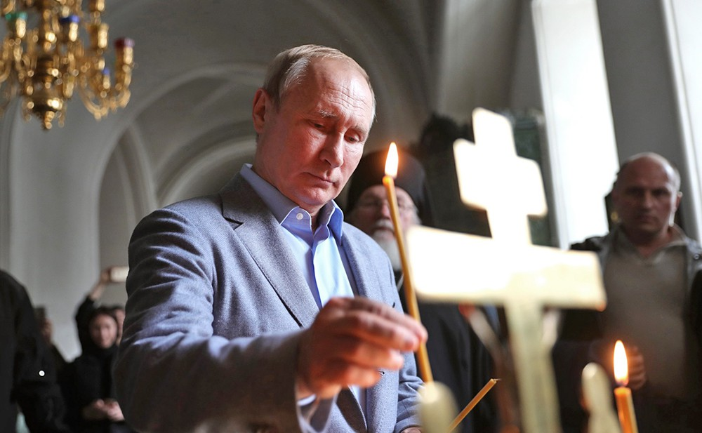 Владимир Путин ставит свечку в храме
