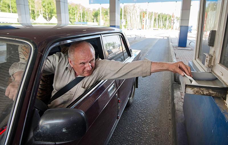 Водитель оплачивает проезд на контрольно-пропускном пункте на платном участке автомобильной дороги