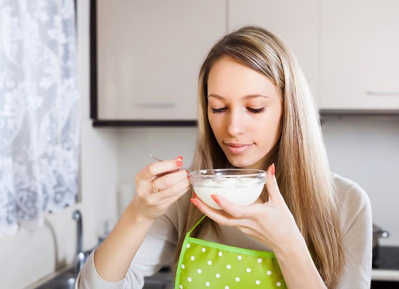 Девушка ест творожную массу