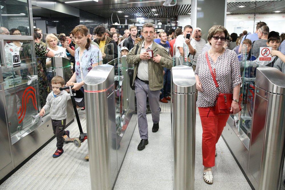 Пассажиры в метро проходят через турникеты
