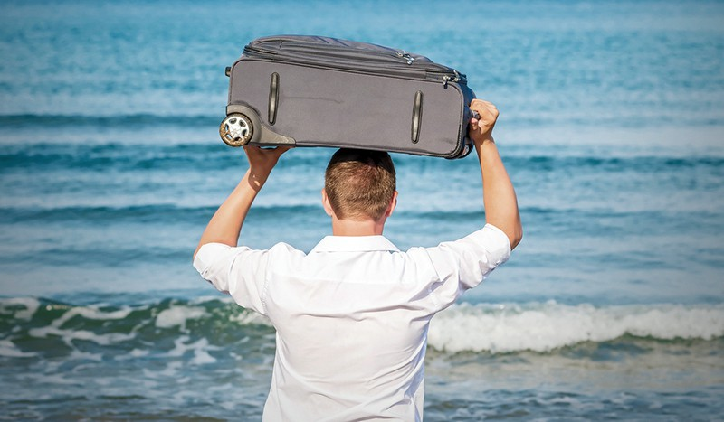 Мужчина с чемоданом на берегу