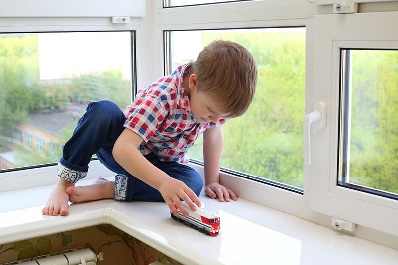 Мальчик сидит на окне