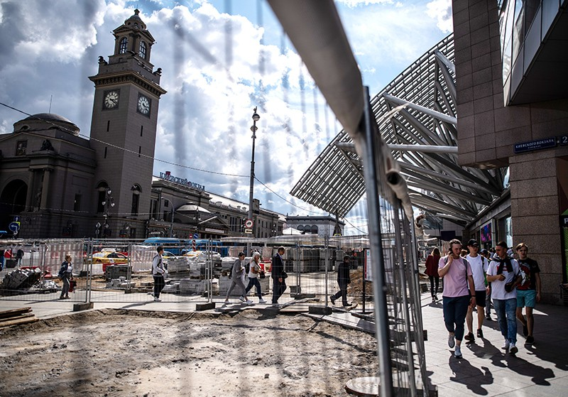 Прохожие на тротуаре возле места проведения работ по благоустройству площади Киевского вокзала