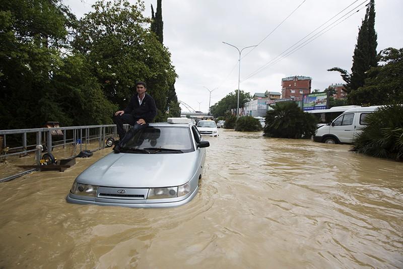 Люди на одной из улиц Сочи, затопленных в результате проливных дождей